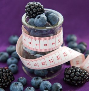 Diet meal. Blackberry and blueberry  in a glass jar with measure